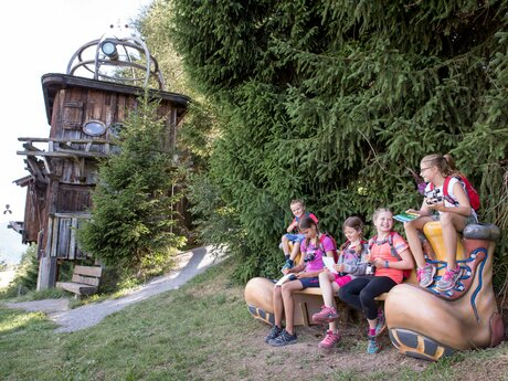 Children sitting on a bench in front of the tree house on the Explorer's Trail in Ladis in Tyrol | © Andreas Kirschner