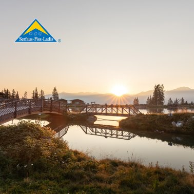 Sunrise at Högsee with bridge, water sun and landscape in Serfaus-Fiss-Ladis, Tyrol, Austria | © Serfaus-Fiss-Ladis Marketing GmbH | Andreas Kirschner